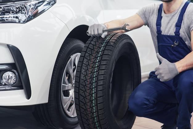 Técnico com uma roupa azul, segurando uma chave inglesa e um pneu enquanto aparece o polegar Foto gratuita