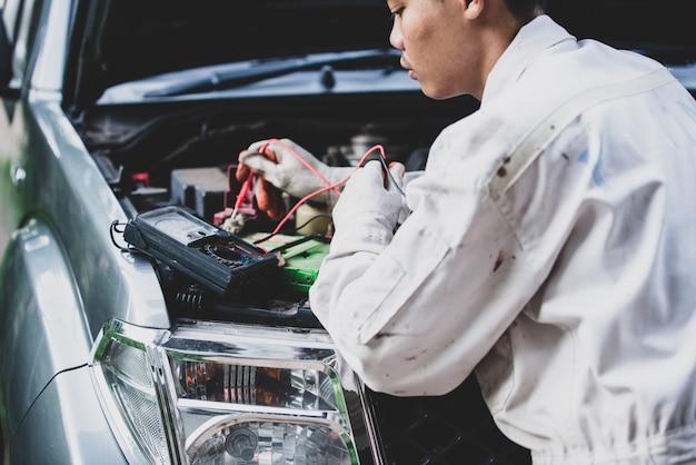 Técnico de automóveis, vestindo um uniforme branco, de pé e segurando uma chave inglesa, que é uma ferramenta essencial para um mecânico Foto gratuita