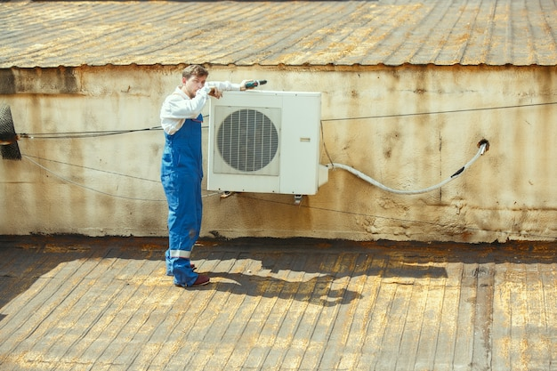Técnico de hvac trabalhando em uma peça de capacitor para unidade de condensação. trabalhador do sexo masculino ou reparador de uniforme reparando e ajustando o sistema de condicionamento, diagnosticando e procurando problemas técnicos. Foto gratuita