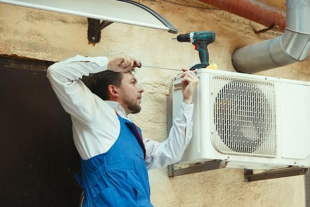 Técnico de hvac trabalhando em uma peça de capacitor para unidade de condensação Foto gratuita