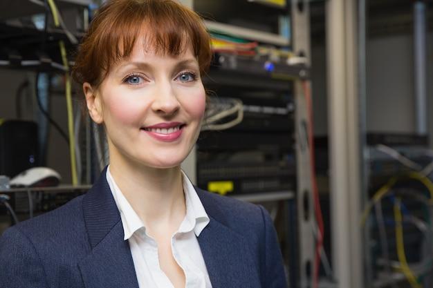 Técnico de informática bonita sorrindo para a câmera ao lado do servidor aberto Foto Premium