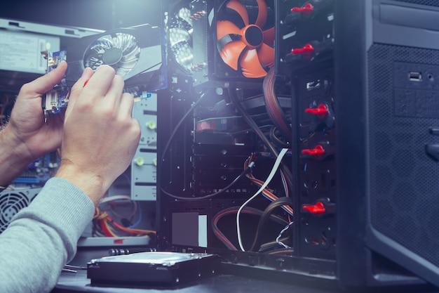Técnico de reparação de um computador, o processo de substituição de componentes na placa-mãe. Foto Premium