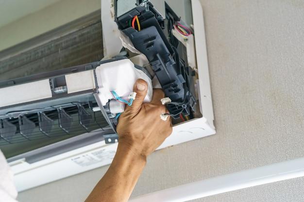 Técnico de serviço é a limpeza, reparação e manutenção de ar condicionado Foto Premium