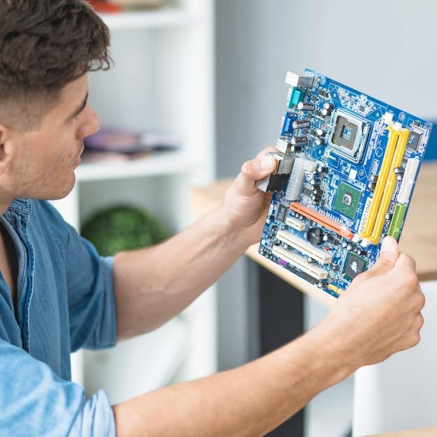 Técnico de ti masculino olhando para pc motherboard Foto gratuita