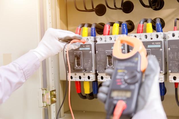 Técnico está medindo tensão ou corrente por voltímetro no painel de controle Foto Premium