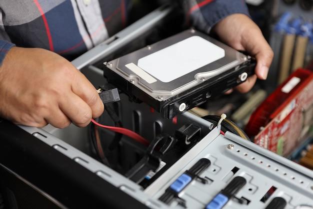 Técnico homem consertar ou atualizar o disco rígido no computador Foto Premium