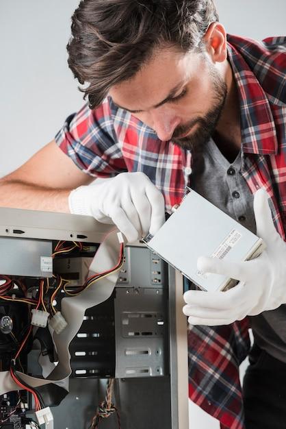Técnico inserindo o cabo de dados sata na unidade de disco rígido Foto gratuita