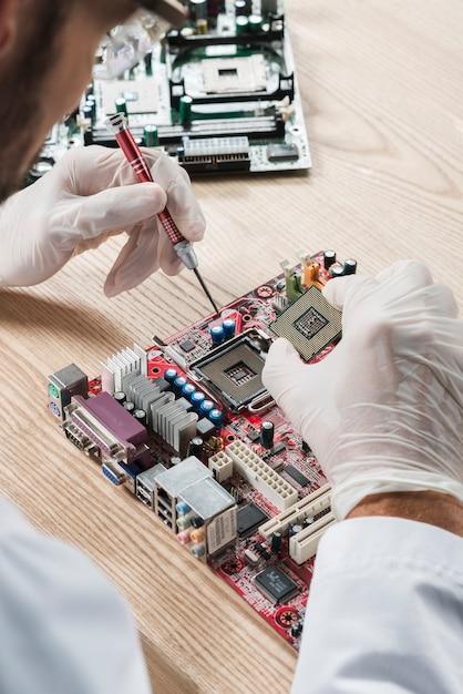 Técnico, inserindo o chip de computador na placa-mãe na mesa de madeira Foto gratuita