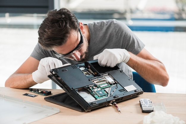 Técnico masculino novo que fixa o computador na mesa de madeira Foto gratuita