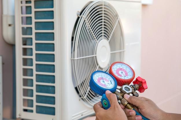 Técnico que usa equipamento de medição para encher condicionadores de ar e verificar a unidade de compressor de ar externo. Foto Premium