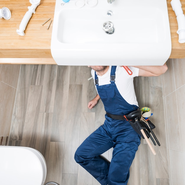 Técnico sanitário deitado sob pia Foto gratuita