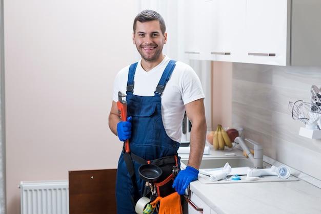 Técnico sanitário sorridente segurando chave Foto Premium
