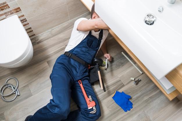 Técnico sanitário trabalhando sob a pia Foto Premium