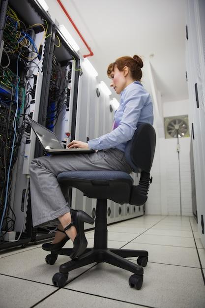 Técnico sentado na cadeira giratória usando laptop para diagnosticar servidores Foto Premium