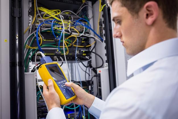 Técnico sério usando analisador de cabo digital no servidor Foto Premium