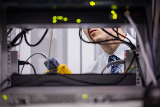 Técnico usando o analisador de cabo digital no servidor Foto Premium