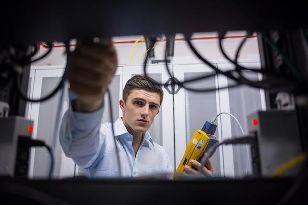 Técnico usando o testador de cabos ao consertar o servidor Foto Premium