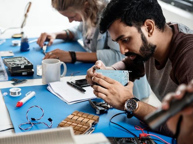 Técnicos elétricos trabalhando em peças eletrônicas Foto gratuita