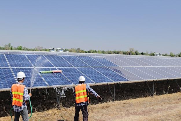Técnicos para limpar células solares em uma planta solar Foto Premium