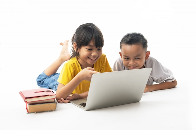 Tecnologia com aprendizagem e educação, grupo de crianças asiáticas olhando no laptop em fundo branco Foto Premium