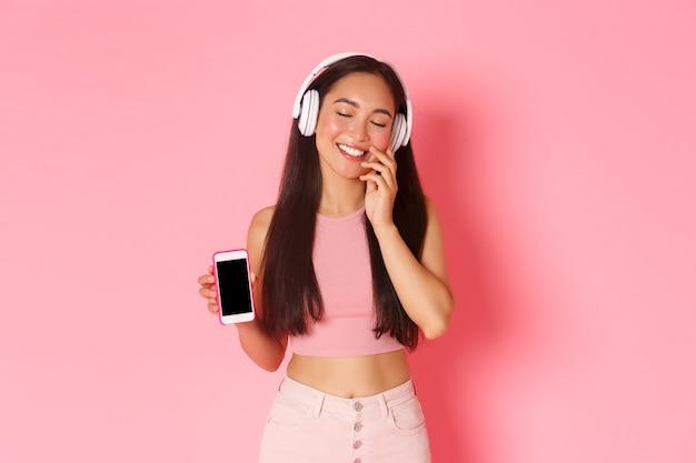 Tecnologia, comunicação e conceito de estilo de vida online. linda garota asiática sonhadora em fones de ouvido, fecha os olhos e toca a bochecha, boba, sonhando acordada enquanto ouve música, mostrando a tela do celular Foto gratuita