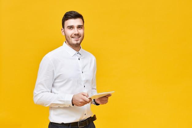 Tecnologia moderna e conceito de dispositivos eletrônicos. elegante positivo jovem gerente usando tablet digital para o trabalho. empresário com roupa formal segurando um computador portátil touch pad Foto gratuita