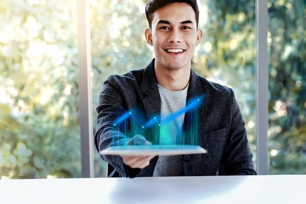 Tecnologia no conceito de negócio. homem feliz apresentando gráfico de alto lucro em tablet digital Foto Premium