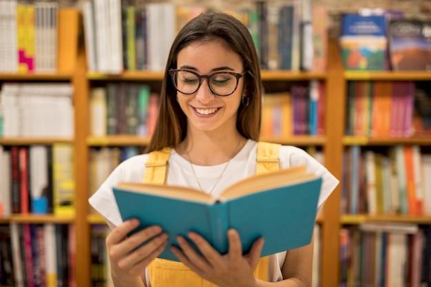 Teen colegial em óculos lendo livro Foto gratuita