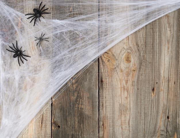 Teia de aranha branca com aranhas negras em um cinza de madeira de tábuas velhas Foto Premium