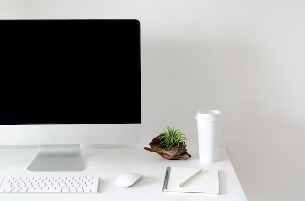 Tela de computador pessoal moderna na mesa branca com uma xícara de café. Foto Premium
