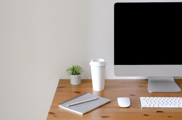 Tela de computador pessoal moderna na mesa de madeira com uma xícara de café. Foto Premium