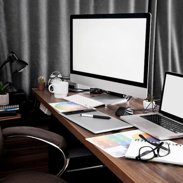 Tela do computador e laptop no espaço de trabalho do escritório com paletas de cores Foto gratuita