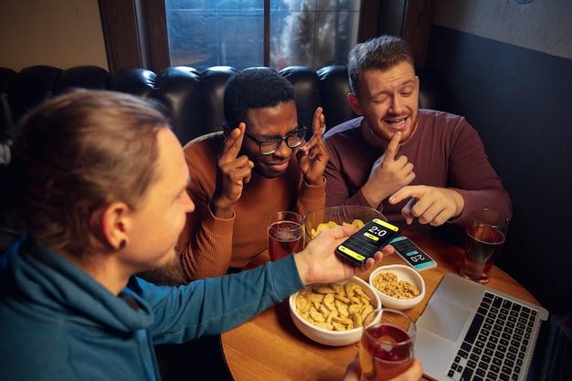Tela do dispositivo com aplicativo móvel para apostas e pontuação. dispositivo com resultados da partida na tela, fãs animados no fundo durante a partida. Foto gratuita