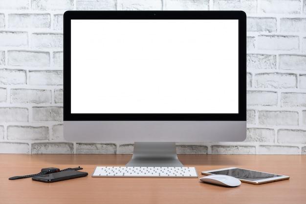 Tela em branco de tudo em um computador com tablet, telefone inteligente e relógio inteligente na mesa de madeira, fundo da parede de tijolo branco Foto Premium