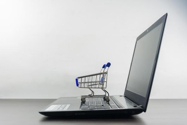 Tela em branco do computador notebook com carrinho de compras na mesa de madeira Foto Premium