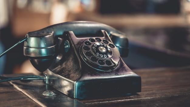 Telefone antigo preto na mesa de madeira Foto Premium