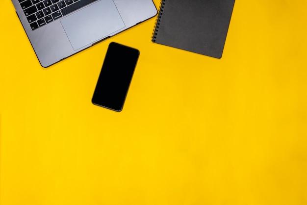 Telefone, bloco de notas preto e laptop Foto gratuita