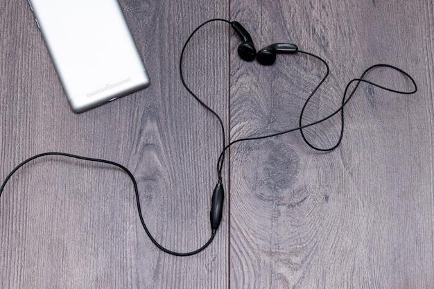 Telefone celular com fones de ouvido em forma ou coração em fundo de madeira. coloque plana, copie o espaço. Foto Premium