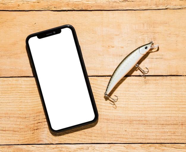 Telefone celular com tela branca e isca de pesca na mesa de madeira Foto gratuita