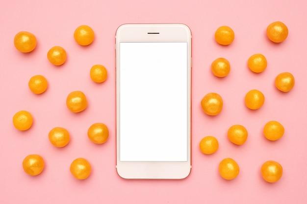 Telefone celular e doces amarelos em um rosa, tecnologia Foto Premium