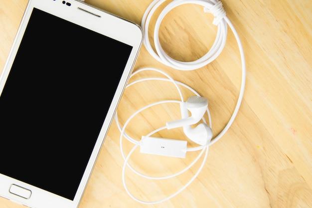Telefone celular e fones de ouvido no fundo de madeira com espaço. Foto Premium