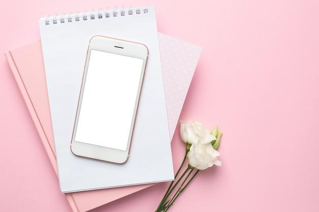 Telefone celular, flor branca e caderno rosa Foto Premium