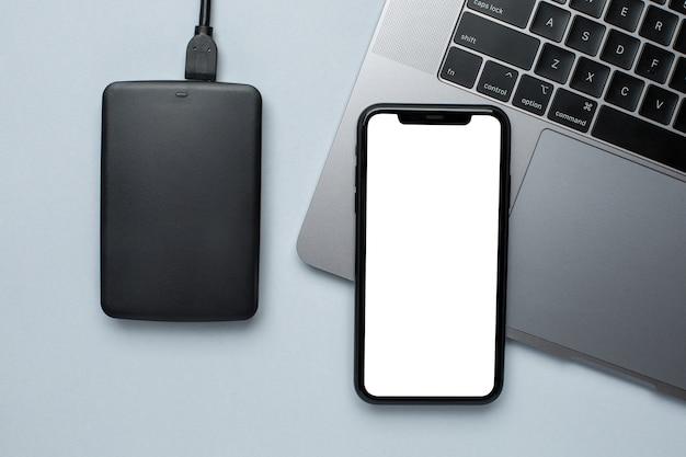 Telefone celular mock up e disco rígido removível com laptop Foto Premium