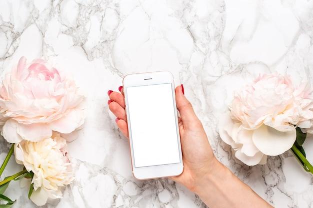 Telefone celular na mão com flores piony brancas e rosa em uma superfície de mármore Foto Premium