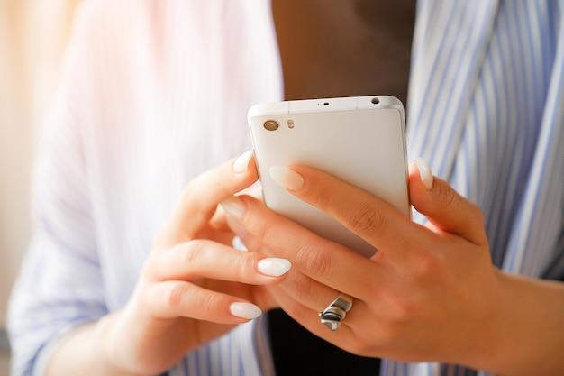 Telefone celular nas mãos de uma mulher elegante ou freelancer. Foto Premium