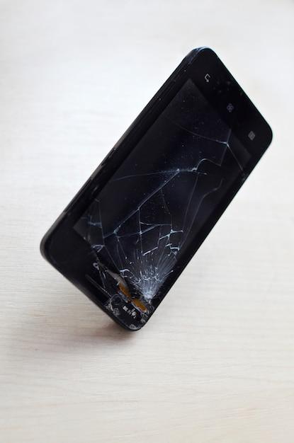 Telefone celular quebrado da tela no fundo cinzento conceito da garantia do seguro e do telefone celular de smartphone vista superior. Foto Premium
