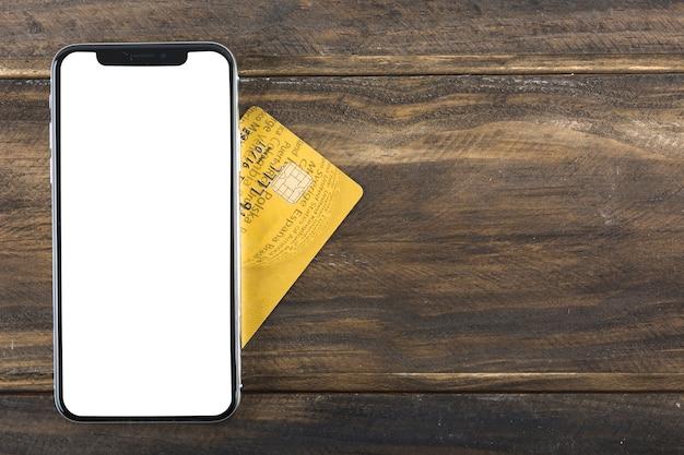 Telefone com cartão de crédito na mesa Foto gratuita