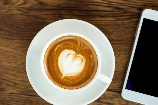 Telefone inteligente com café de latte art em fundo de madeira Foto Premium