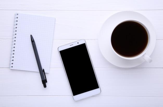 Telefone inteligente com notebook e xícara de café sobre fundo branco de madeira Foto Premium