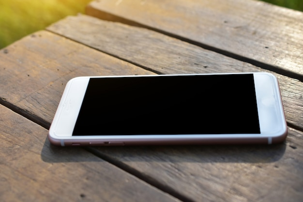 Telefone inteligente móvel está na mesa de madeira Foto Premium